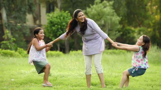 adult woman playing with her daughter in the park, delhi, india - ziehen stock-videos und b-roll-filmmaterial