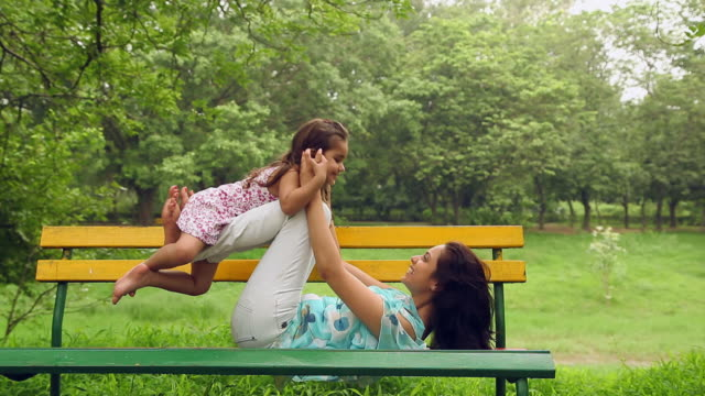 vidéos et rushes de adult woman playing with her daughter in the park, delhi, india - banc public
