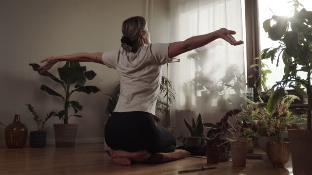 adult woman practising yoga at home by the window - blondes haar stock-videos und b-roll-filmmaterial