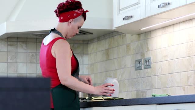 vidéos et rushes de femme adulte préparant la nourriture dans la cuisine - pin up