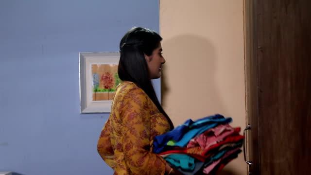 Adult woman putting clothes into cupboard, Delhi, India