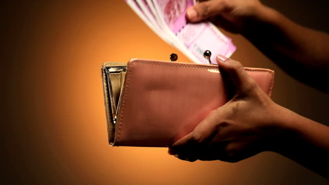 adult woman putting indian two thousand banknotes in to her purse, delhi, india - sfondo marrone video stock e b–roll