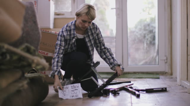 Adult woman putting together flatpack shelving