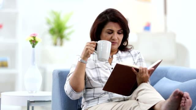 vídeos y material grabado en eventos de stock de adult woman reading book in the home, delhi, india - planta del pie