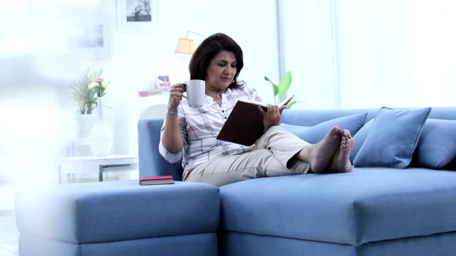 Adult woman reading book in the house, Delhi, India