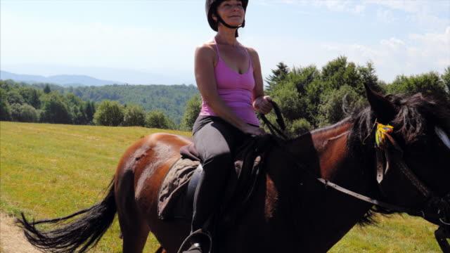 Volwassen vrouw riding bruin paard dragen van de helm in Bergen