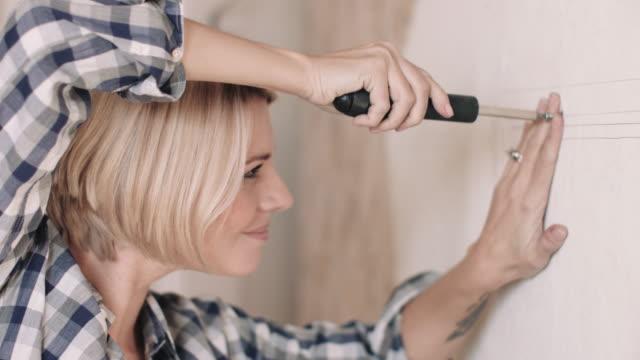 adult woman screwing into the wall of new home - solo una donna di età media video stock e b–roll