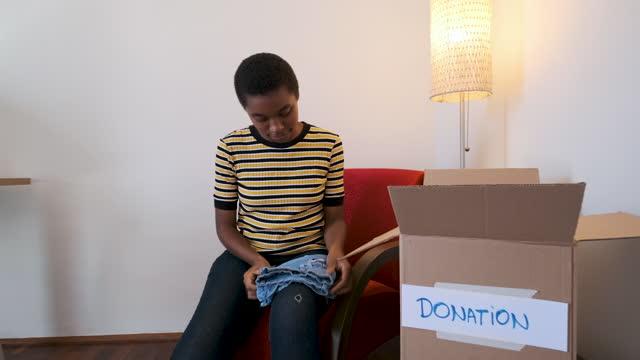 vídeos y material grabado en eventos de stock de mujer adulta que selecciona qué ropa usar para la donación - sólo mujeres jóvenes
