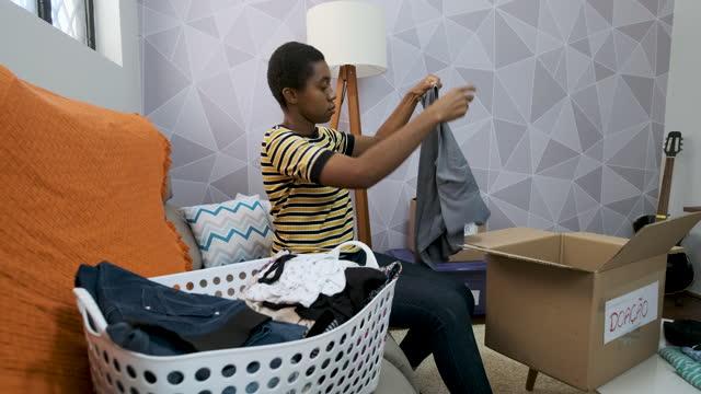 vídeos y material grabado en eventos de stock de mujer adulta clasificando ropa para donación - sólo mujeres jóvenes