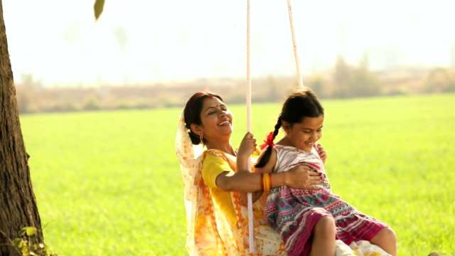 vidéos et rushes de adult woman swinging with her daughter in the farm, haryana, india - prendre sur les genoux