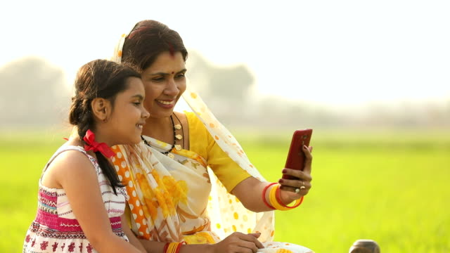 Adult woman taking self-portrait photography with her daughter, Haryana, India