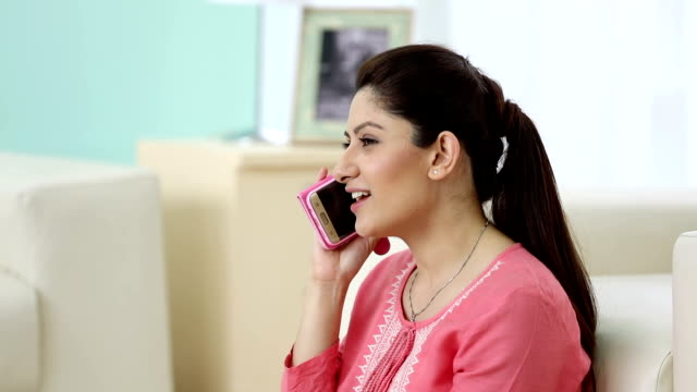 vídeos de stock, filmes e b-roll de adult woman talking on mobile phone at home, delhi, india - camisas