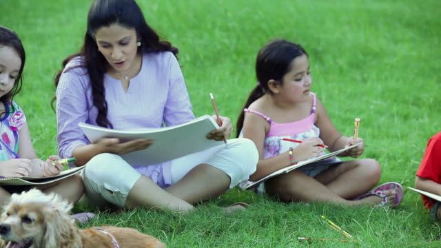 adult woman teaching kids in the park, delhi, india - sketch pad stock videos and b-roll footage