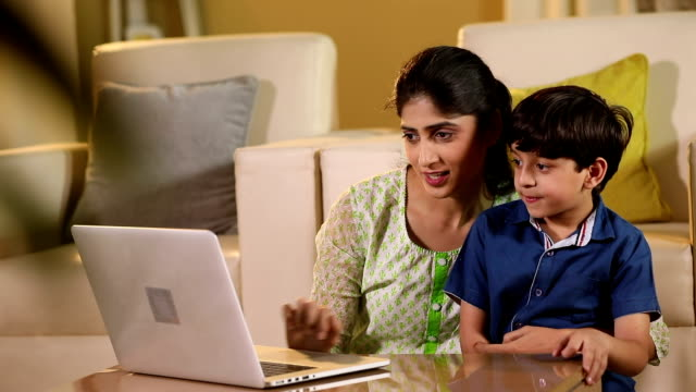 Adult woman teaching laptop to her son at home, Delhi, India