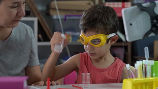 Adult Woman Teaching Little Boy Chemistry In Lab