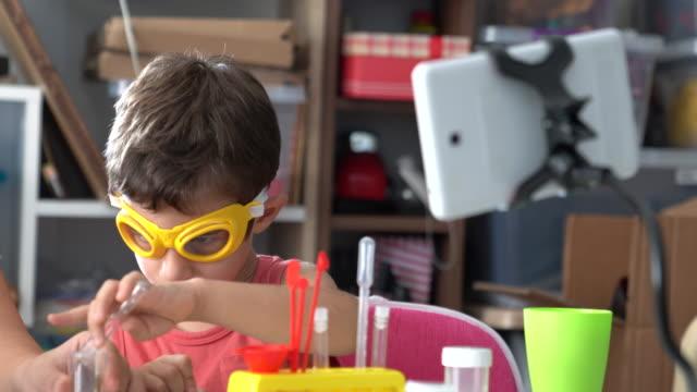 Erwachsene Frau unterrichtet kleine Junge Chemie im Labor