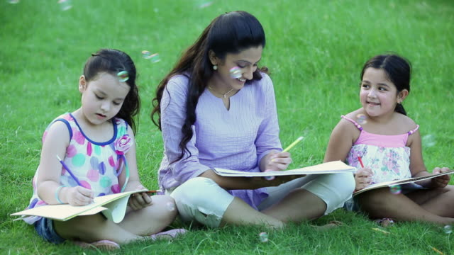 Adult woman teaching to her daughters in the park, Delhi, India