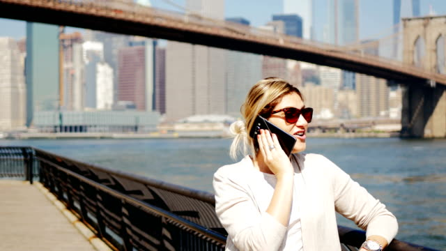 adult woman using phone in new york city - brooklyn bridge stock videos & royalty-free footage