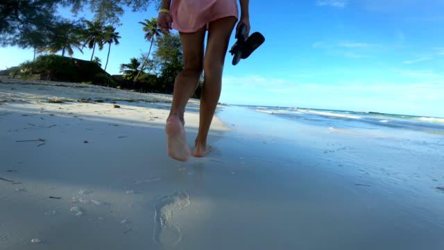 donna adulta che cammina sulla spiaggia sabbiosa durante le vacanze tropicali - evitare video stock e b–roll