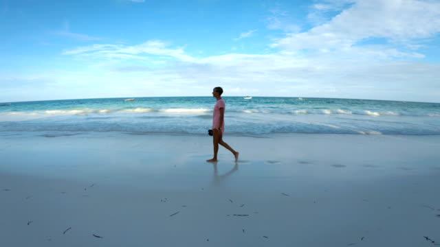 トロピカル・バケーションズの砂浜で大人の女性が歩いている - 全身点の映像素材/bロール