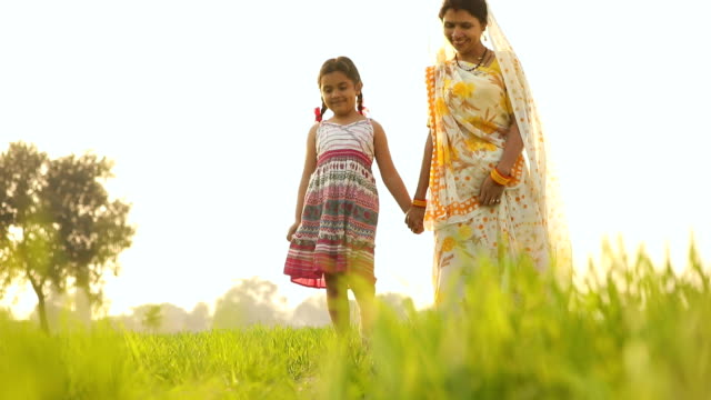 Adult woman walking with her daughter in the farm, Haryana, India
