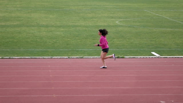 Adult Woman With Long Hair Running In Stadium