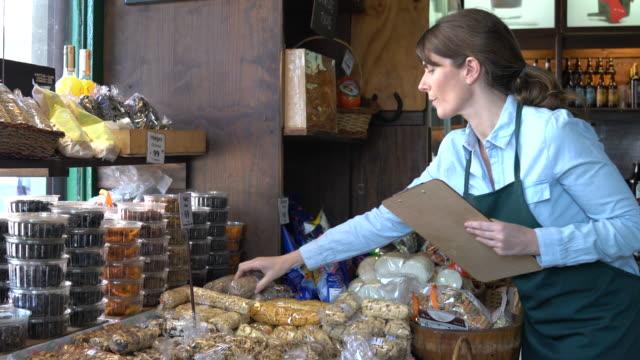 デリカテッセンで働く大人の女性は、クリップボードに何かを書き留め、在庫をやっています - 棚点の映像素材/bロール
