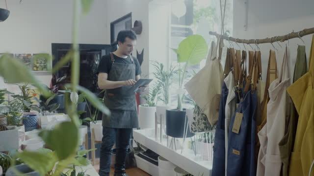 vidéos et rushes de travailleur adulte vérifiant l'inventaire sur la tablette numérique dans sa boutique de botanique - détermination
