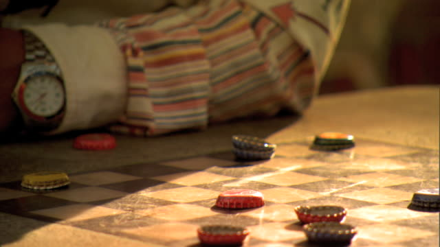 vs adult young adult male hands playing checkers adult moving rightsideup bottle caps young adult male using upsidedown bottle caps crowning king w/... - bottle cap stock videos & royalty-free footage