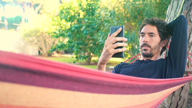 vídeos y material grabado en eventos de stock de adult young man in his hammock using a smartphone - portability
