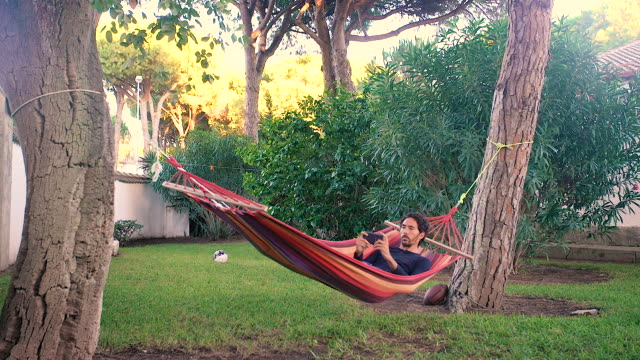 vídeos de stock, filmes e b-roll de adult young man in his hammock using a smartphone - rede de dormir