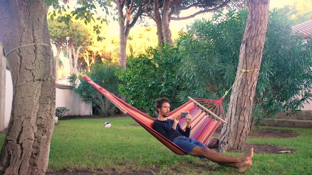 vídeos de stock e filmes b-roll de adult young man in his hammock using a smartphone - cama de rede