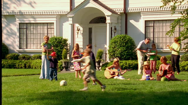 adults and children play in a front yard on a beautiful summer day. - large family stock videos & royalty-free footage