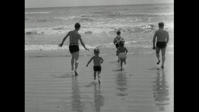 adults and children run into the surf on sandy beach; 1950 - less than 10 seconds stock videos & royalty-free footage