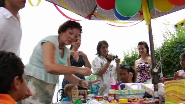 adults and children standing and sitting around umbrella covered table at birthday party / man filming home movies with digital camcorder and woman serving ice cream / new jersey - digital camcorder stock videos & royalty-free footage