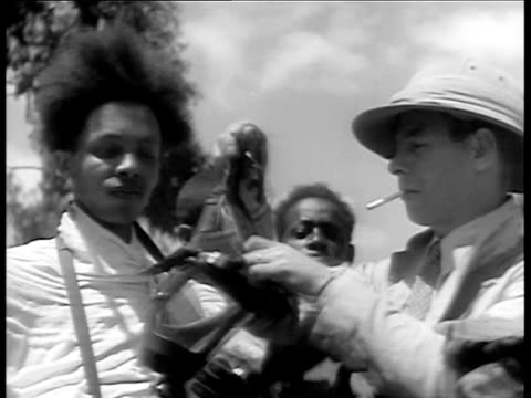 vidéos et rushes de adults and children trying on gas masks / ethiopia men getting fitted for gas mask / man blowing cigarette smoke at gas mask to test / kids trying on... - 1935
