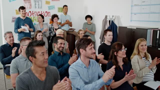 Adults attending an employment and career course applauding their teacher