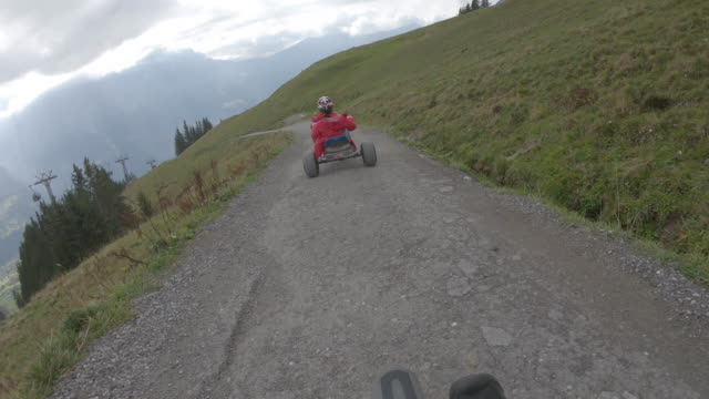 adults descend mountain track on go carts, through alpine meadow - 40 49 years stock videos & royalty-free footage