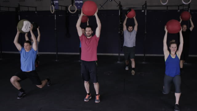 Adults doing a lunging workout together with a medicine ball