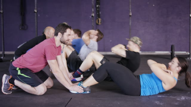 Adults doing ab workouts together with a medicine ball