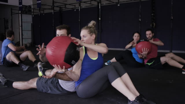 Adults Doing Ab Workouts Together With A Medicine Ball Stock Footage Video