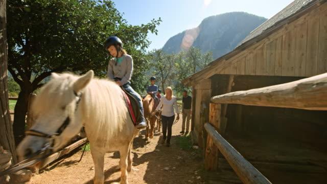 vídeos de stock e filmes b-roll de adults guiding horses carrying children on their backs on the sunny ranch - cavalgar