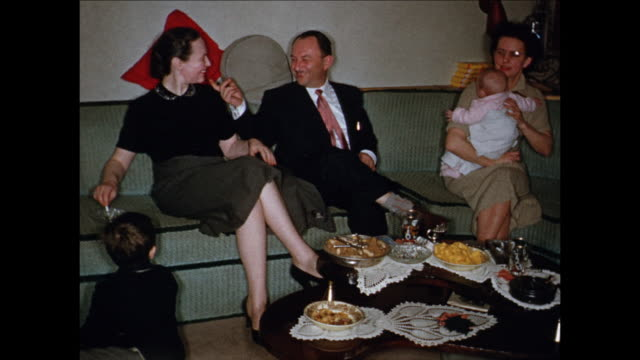 vidéos et rushes de 1955 montage adults on couch, drinking, playing with baby (12 months) / toronto, canada - 12 17 mois
