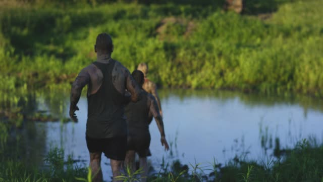 Adults Participating In A Mud Run