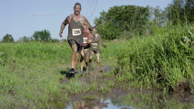 大人の泥の実行に参加しています。 - 障害物コース点の映像素材/bロール