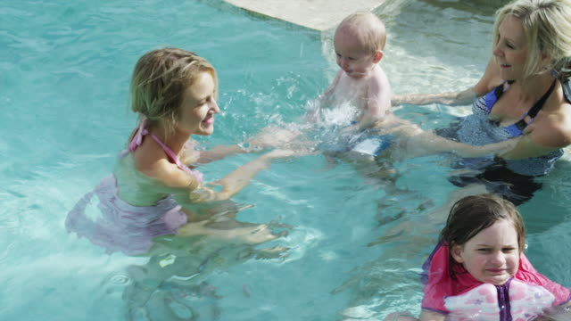MS Adults playing with kids (6-11 months, 4-5 years) in pool / Cedar Hills, Utah, USA