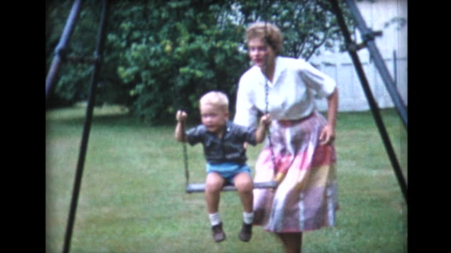 stockvideo's en b-roll-footage met 1958 adults take turns pushing boy on a swing - speeltuin