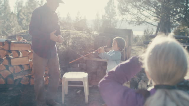 adults with boy by campfire - montana stock-videos und b-roll-filmmaterial
