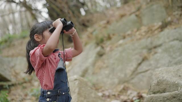 äventyr och utforskning av ett barn, sidovy av asiatisk tjej som har en naturlig resa, fritidsaktiviteter för att se ett vilddjur med kikare medan du vandrar för att hålla lyckan ögonblick i en tropisk skog. - 6 7 år bildbanksvideor och videomaterial från bakom kulisserna
