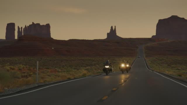 vídeos y material grabado en eventos de stock de adventure motorcycles approaching on freeway at dusk / monument valley, utah, united states - valle monumento